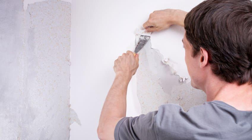 Heimwerker entfernet Tapete von der Wand