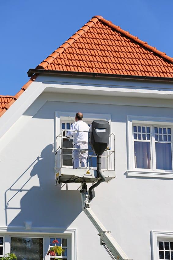 Maler auf Arbeitsbühne beim Fensterstreichen